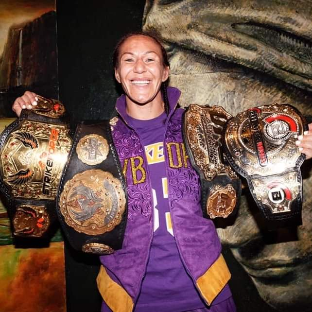 Chris Cyborg holding up her 4  different promotional belts.